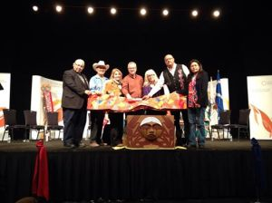Mennonites Tim Dyck (fourth from L) and Hildebrand (5th from L) present a quilt to Commissioners and Survivor Representatives at the Truth and Reconciliation Commission Edmonton National Event, March 2014.