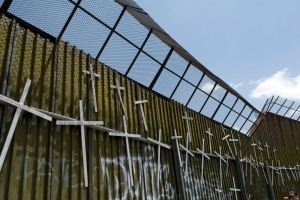 Crosses hang on the Mexican side of the border wall in Nogales, Mexico, commemorating the 4,000 people who have lost their lives attempting to cross the desert in search of a better life in the United States.  Copyright:Tim Hoover/MCC