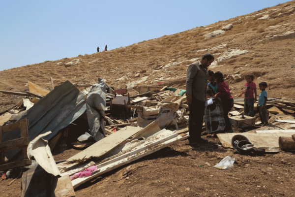 People pick through rubble at the site of a demolition in Wadi Sneysel, in the West Bank near East Jerusalem. Photo credit: Lutheran World Relief.