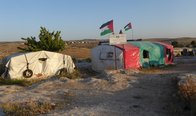 Palestinian flags fly over some of the temporary homes in the village of Susiya. Photo credit: P. Moore, EAPPI