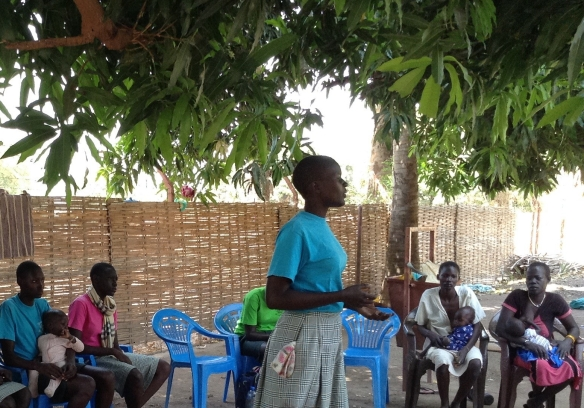 Peace Club member speaking to local women about conflict resolution