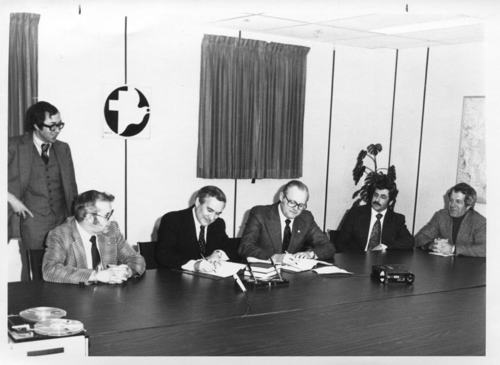 Five men sitting at a conference room table signing a document with one man standing behind them.