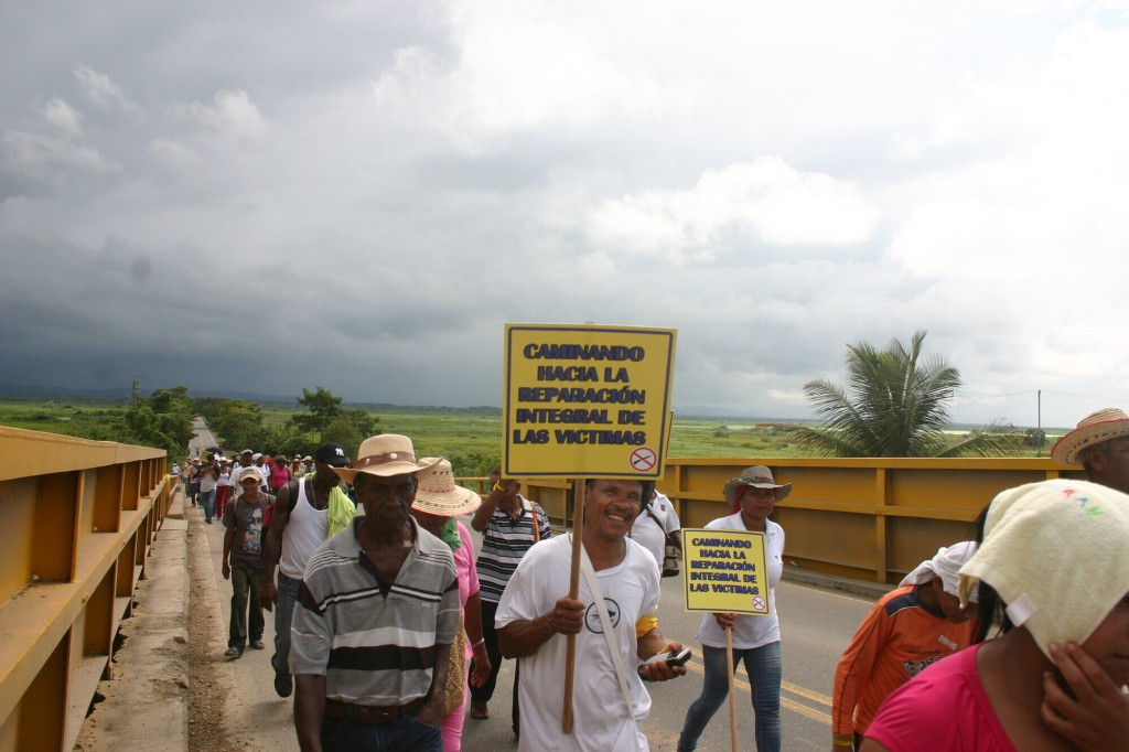 A large group of people march over a bridge carrying signs.