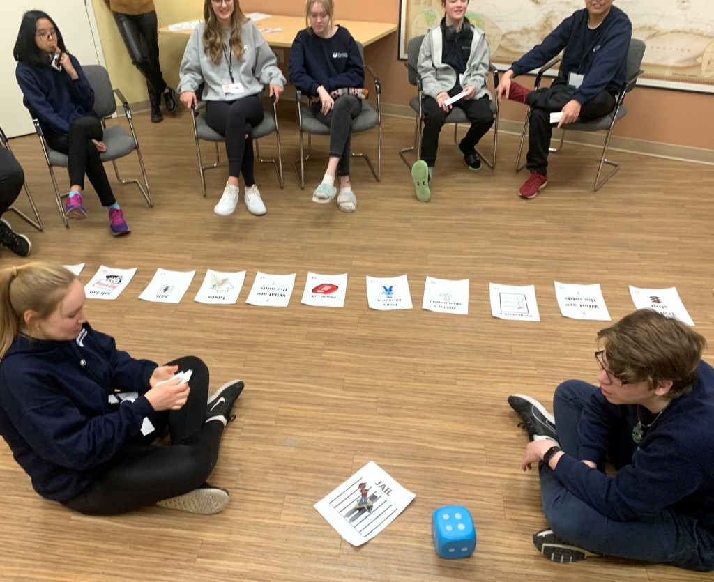 Students sit in a circle around game pieces on the floor.