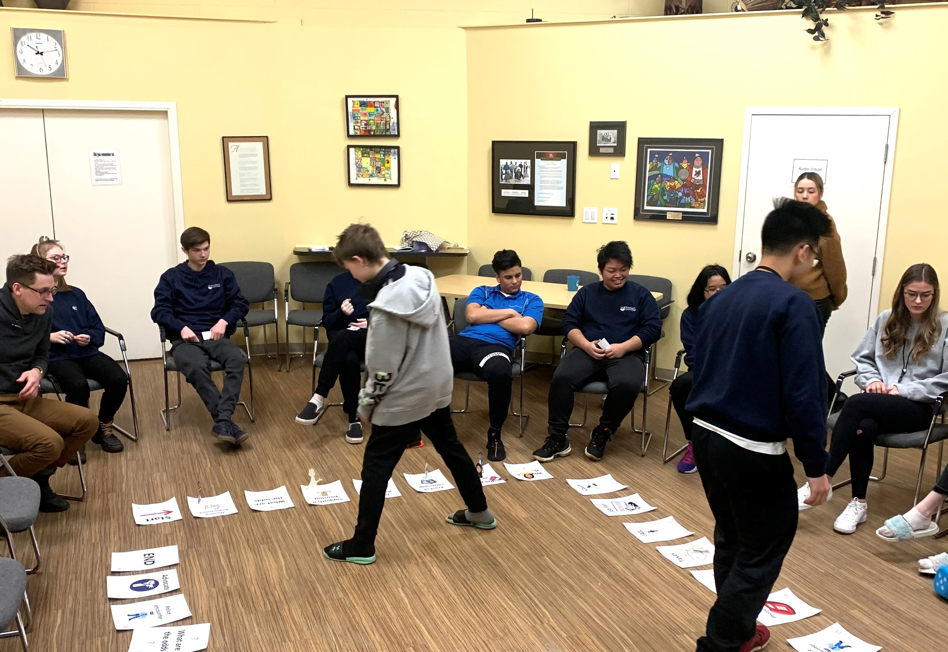 A circle of students watch as two classmates move around a game board.