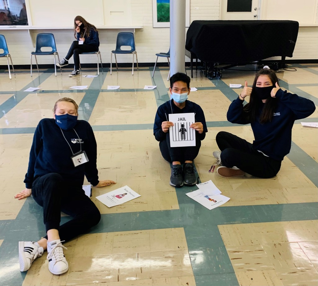 3 students sit on the floor and one holds a piece of paper representing Jail.